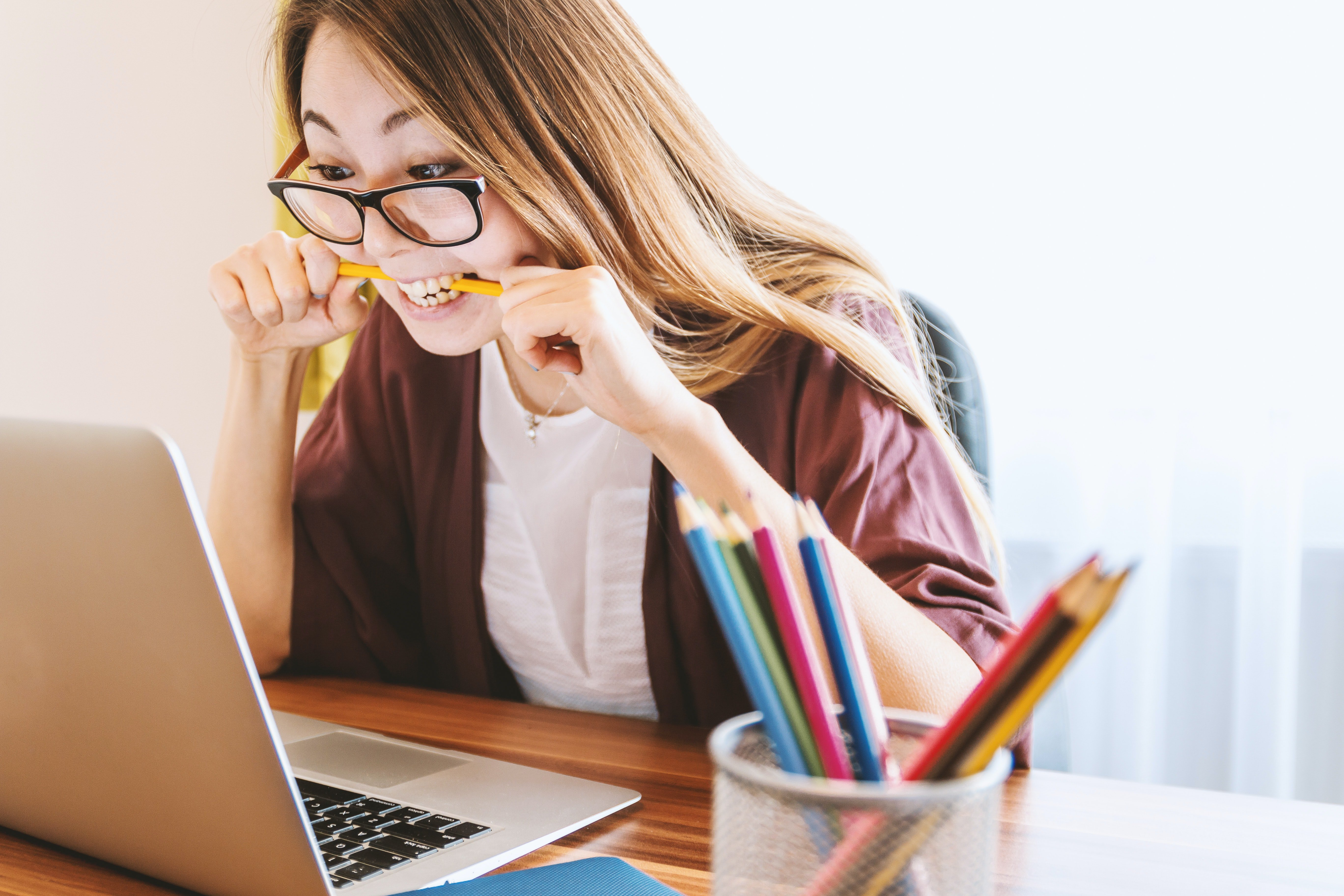 woman biting pencil while looking at laptop